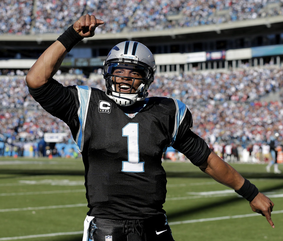 Photo - Carolina Panthers quarterback Cam Newton (1) celebrates a Carolina Panthers wide receiver Steve Smith touchdown against the San Francisco 49ers during the first half of a divisional playoff NFL football game, Sunday, Jan. 12, 2014, in Charlotte, N.C. (AP Photo/Chuck Burton)