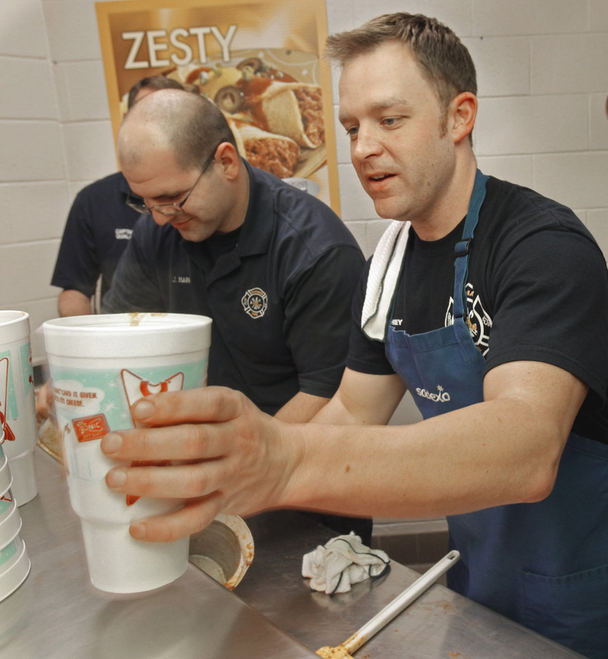 Firefighters Jeff Harris (left) and Chad Humphrey dish up chili to go at the annual Police and Firemen\'s Benefit Chili Supper on Thursday, Jan. 12, 2012, in Norman, Okla. Photo by Steve Sisney, The Oklahoman