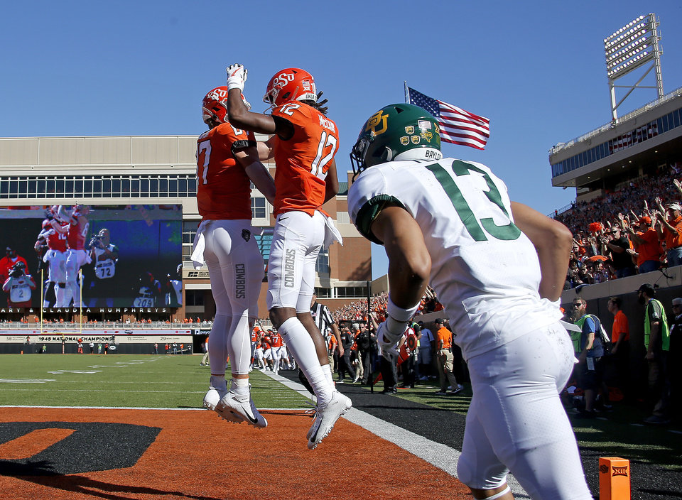 Photo - Oklahoma State's Jordan McCray (12) celebrates his touchdown with Logan Carter (87) as Baylor's Raleigh Texada (13) runs off the field in the first quarter during the college football game between Oklahoma State University and Baylor at Boone Pickens Stadium in Stillwater, Okla., Saturday, Oct. 19, 2019. [Sarah Phipps/The Oklahoman]