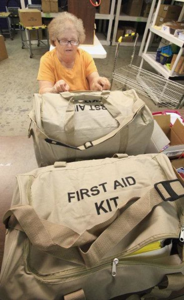 Photo - NewView employee Joan Kuykendall assembles 50-person first aid kits at NewView in Oklahoma City Monday.  PAUL B. SOUTHERLAND - PAUL B. SOUTHERLAND