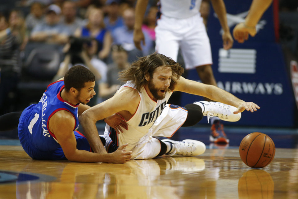 Photo - Charlotte Bobcats forward Josh McRoberts, right, fights for a loose ball against Philadelphia 76ers guard Michael Carter-Williams, left,  during the first half of an NBA basketball game in Charlotte, N.C., Saturday, April 12, 2014. (AP Photo/Chris Keane)