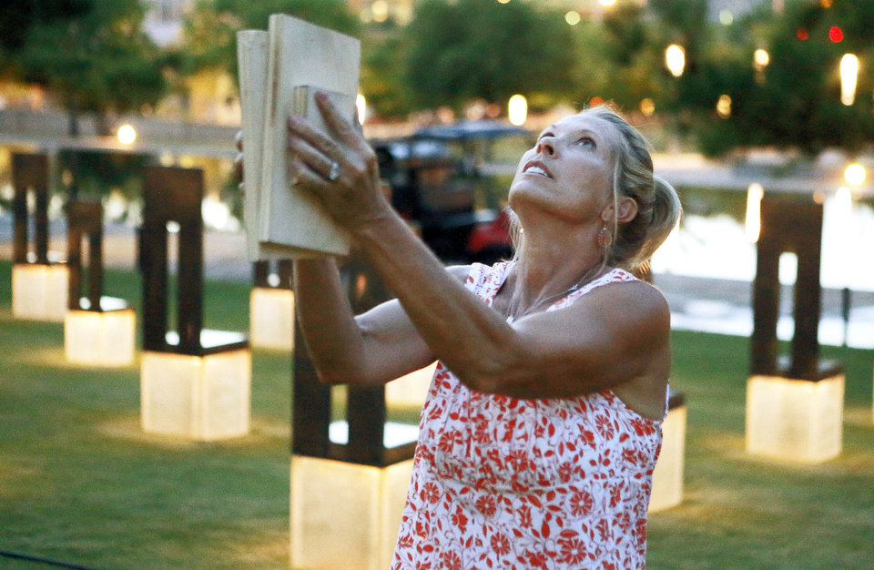 Photo - Debi Bays bangs boards together Tuesday at the Oklahoma City National Memorial. Bays has helped with bird abatement there, which has been besieged by birds this summer. PHOTO BY BRYAN TERRY, THE OKLAHOMAN