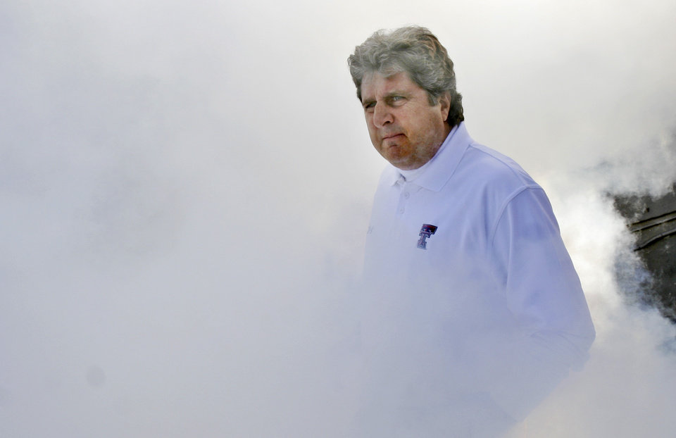 Photo - Texas Tech head football coach Mike Leach walks through dry ice smoke before the start of the NCAA college football game against Baylor in Lubbock, Texas, Saturday, Nov. 29, 2008.  (AP Photo/LM Otero)  ORG XMIT: TXMO106