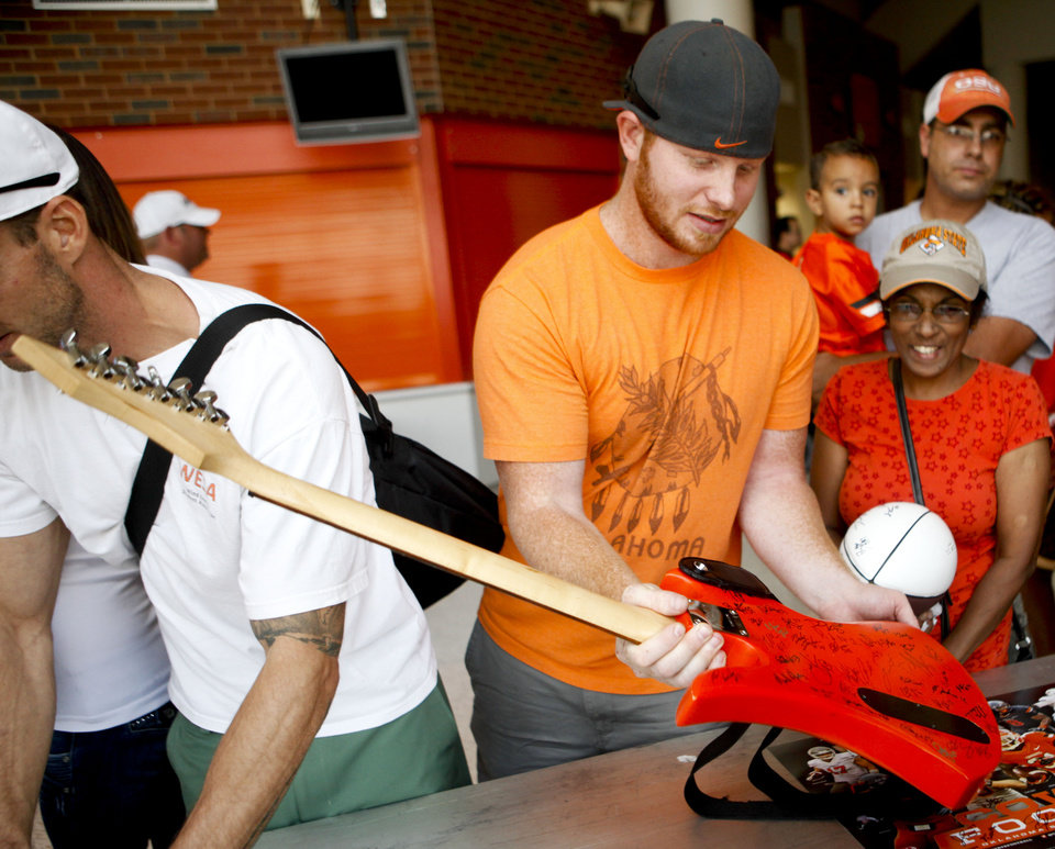 Kody Bickerstaff, 24 of Stillwater, has his custom painted Pistol Pete guitar signed by football players at fan appreciation day at Gallagher-Iba Arena on August 3, 2013. KT King, For The Oklahoman