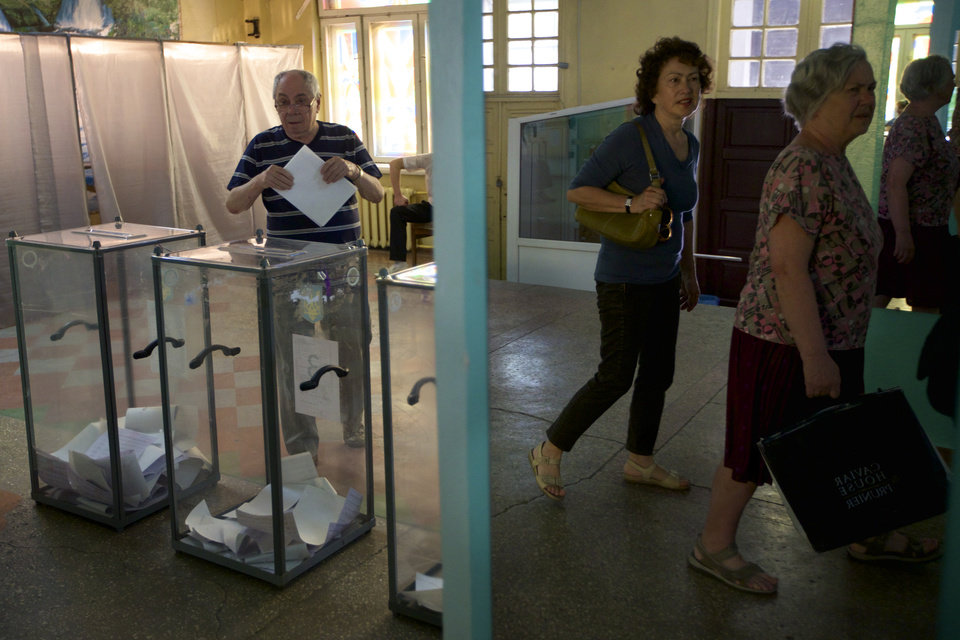 Photo - A Ukrainian man casts his ballot as other voters arrive at a polling station in Mariupol, Ukraine, on Sunday, May 25, 2014. Ukraine's critical presidential election got underway Sunday under the wary scrutiny of a world eager for stability in a country rocked by a deadly uprising in the east. (AP Photo/Ivan Sekretarev)