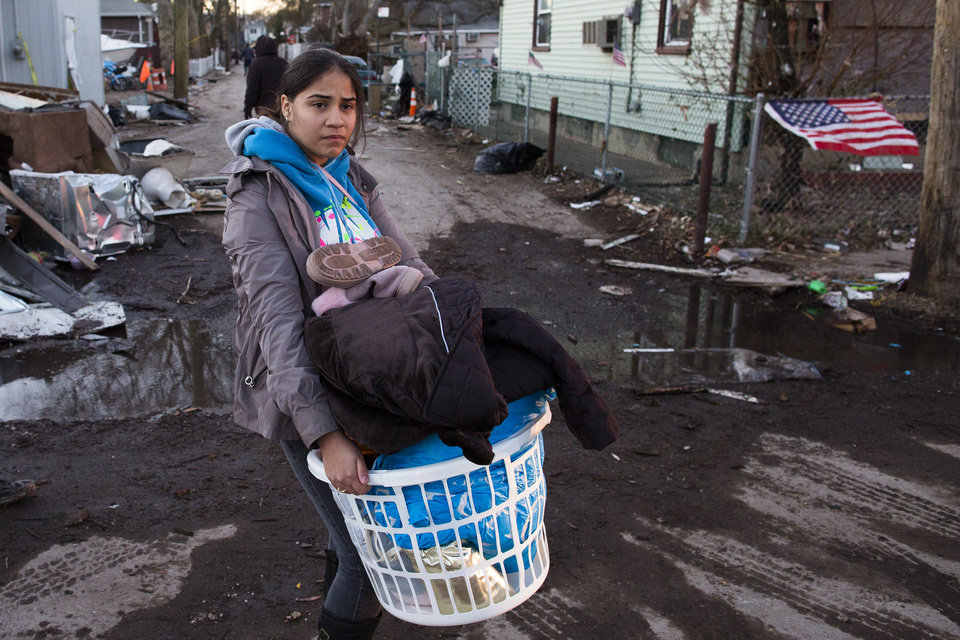 Photo -   A resident of Staten Island's New Dorp Beach neighborhood carries a basket full of clothes and other items on her street that was devastated by Superstorm Sandy, Monday, Nov. 5, 2012, in New York. Although many areas of the metropolitan area are beginning to return to normal, neighborhoods of Staten Island's southern shore remain without power as the cleanup continues. (AP Photo/ John Minchillo)