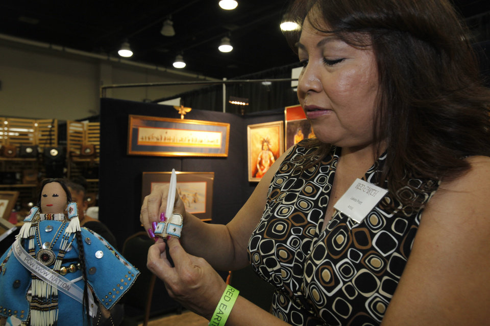 Laketa Pratt adjusts the headpiece on her award winning doll at the Red Earth Festival in Oklahoma City on Friday, June 7, 2013. Photo by Aliki Dyer, The Oklahoman