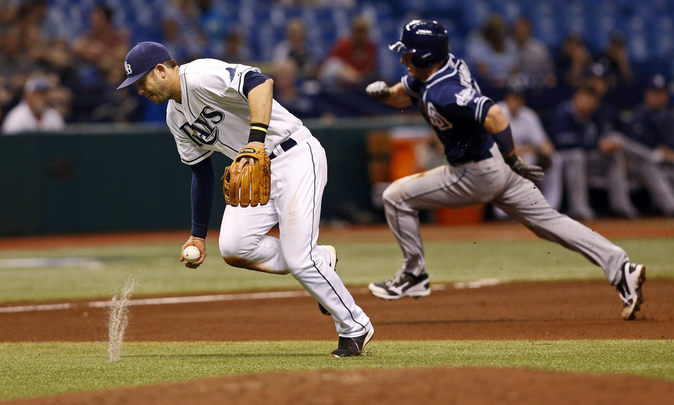 Photo - Tampa Bay Rays third baseman Evan Longoria, left, fields a ball hit by San Diego Padres' Everth Cabrera as Chris Denorfia rounds the bases behind him during the fourth inning of an interleague baseball game, Friday, May 10, 2013, in St. Petersburg, Fla. (AP Photo/Mike Carlson)