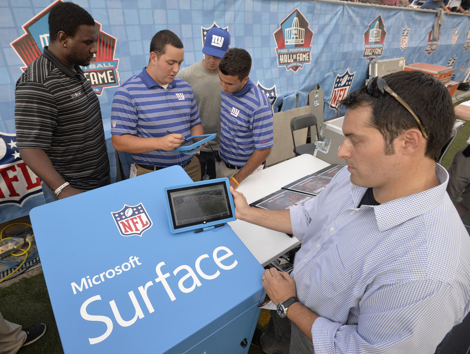 Photo - John Nisi, chief technology officer for Microsoft, holds up a Surface tablet before the New York Giants play the Buffalo Bills at the Pro Football Hall of Fame exhibition NFL football game Sunday, Aug. 3, 2014, in Canton, Ohio. Tablets will be allowed on the sidelines for the first time starting with Sunday's Hall of Fame game, though they won't exactly be running the most cutting-edge apps. The devices will replicate the old system of transmitting still photos to the field _ but faster, clearer and in color. (AP Photo/David Richard)