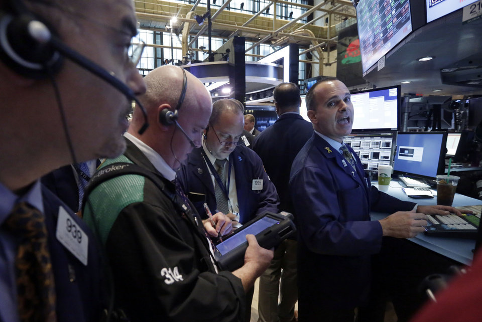 Photo - Specialist John Alatzas, right, directs trades in shares of Walgreen on the floor of the New York Stock Exchange Wednesday, Aug. 6, 2014. Walgreen fell after the drug store company said it will no longer pursue an overseas reorganization that would have trimmed the amount of U.S. taxes it pays. (AP Photo/Richard Drew)