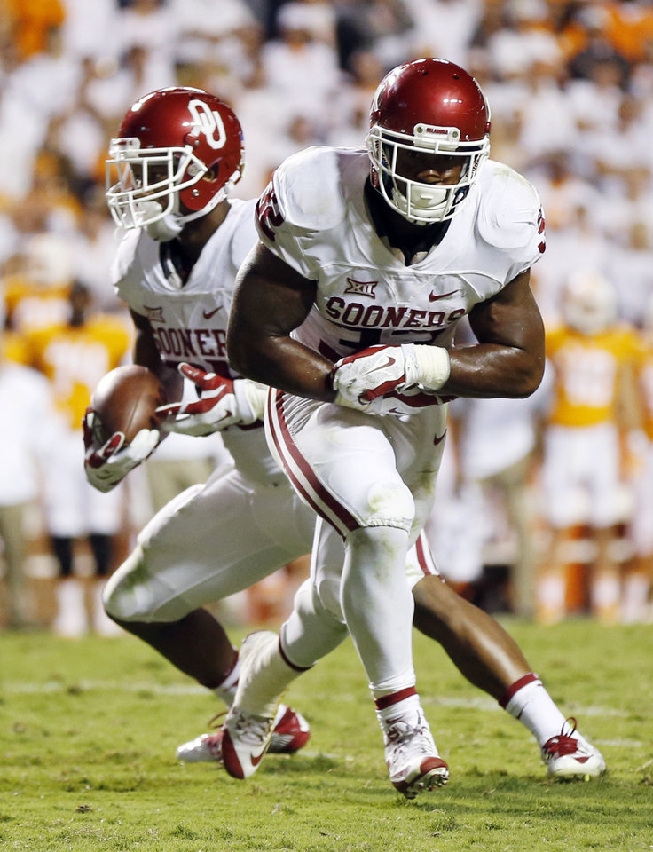Photo - Oklahoma's Joe Mixon (25) keeps the ball after faking a handoff to Samaje Perine (32) during the college football game between the Oklahoma Sooners (OU) and the Tennessee Volunteers at Neyland Stadium in Knoxville, Tennessee, Saturday, Sept. 12, 2015. OU won 31-24 in double overtime. Photo by Nate Billings, The Oklahoman
