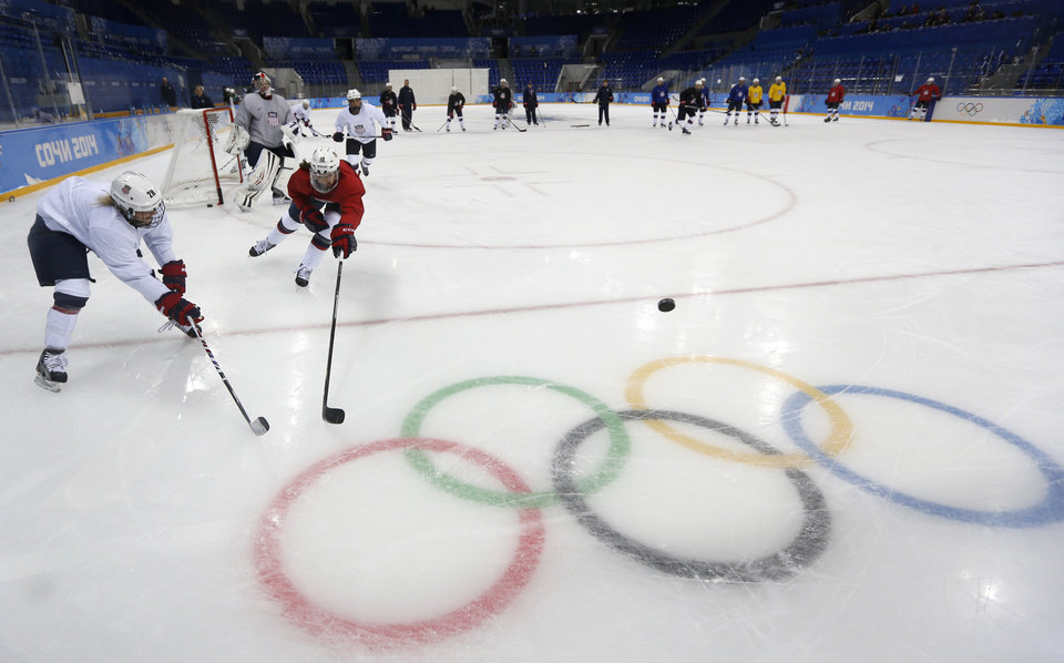 Photo - Meghan Duggan, right, of the U.S. women's ice hockey team challenges her teammate Amanda Kessel, left, during their practice session ahead of the 2014 Winter Olympics, Thursday, Feb. 6, 2014, in Sochi, Russia. (AP Photo/Petr David Josek)