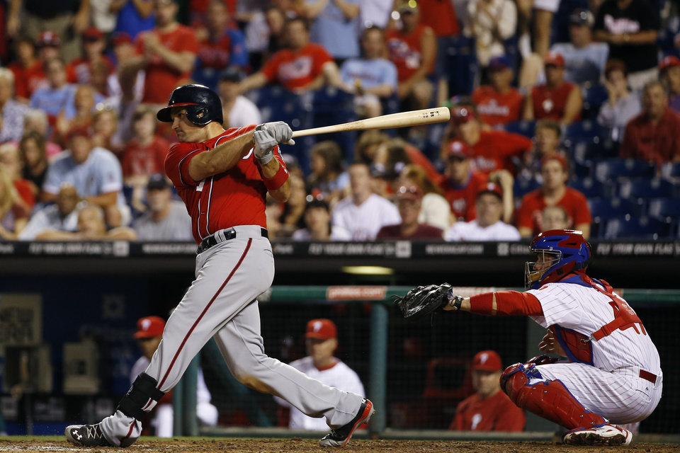 Photo - Washington Nationals' Ryan Zimmerman, left, follows through after hitting a go-ahead RBI-single off Philadelphia Phillies relief pitcher Jake Diekman during the 10th inning of a baseball game, Saturday, July 12, 2014, in Philadelphia. Washington won 5-3 in 10 innings. At right is catcher Koyie Hill. (AP Photo/Matt Slocum)