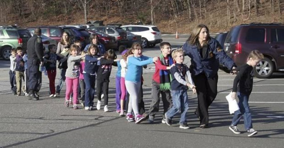 In this photo provided by the Newtown Bee, Connecticut State Police lead children from the Sandy Hook Elementary School in Newtown, Conn., following a reported shooting there Friday, Dec. 14, 2012. (AP Photo/Newtown Bee, Shannon Hicks)