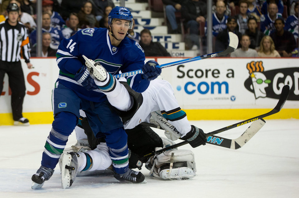 Vancouver Canucks' Alex Burrows, left, checks San Jose Sharks' Dan Boyle in front of goalie Antti Niemi, of Finland, during the first period of an NHL hockey game, Thursday, Nov. 14, 2013 in Vancouver, British Columbia.  (AP Photo/The Canadian Press, Darryl Dyck)