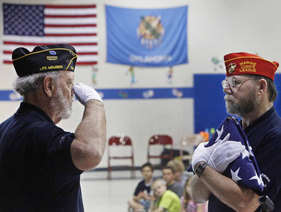 Don Kasper salutes the flag held by Harmon Thompson,  during a flag folding demonstration by the Veteran's School Flag Program members, at Prairie Vale Elementary School, Thursday, March 15, 2012.  Photo By David McDaniel/The Oklahomen