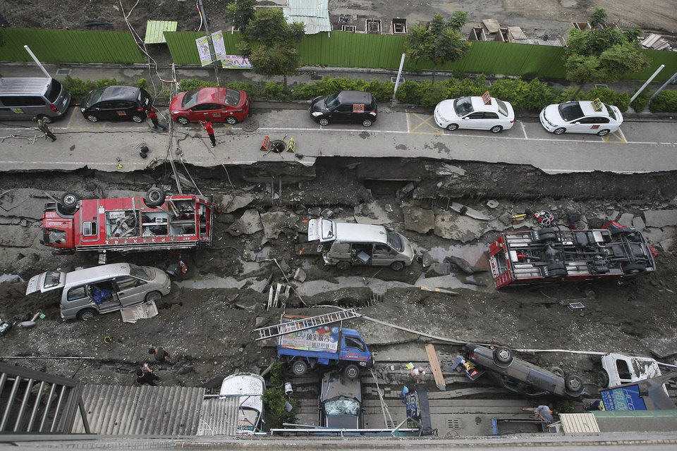 Photo - Vehicles are left lie in a destroyed street following multiple explosions from an underground gas leak in Kaohsiung, Taiwan, early Friday, Aug. 1, 2014. A massive gas leakage early Friday caused five explosions that killed scores of people and injured over 200 in the southern Taiwan port city of Kaohsiung. (AP Photo) TAIWAN OUT