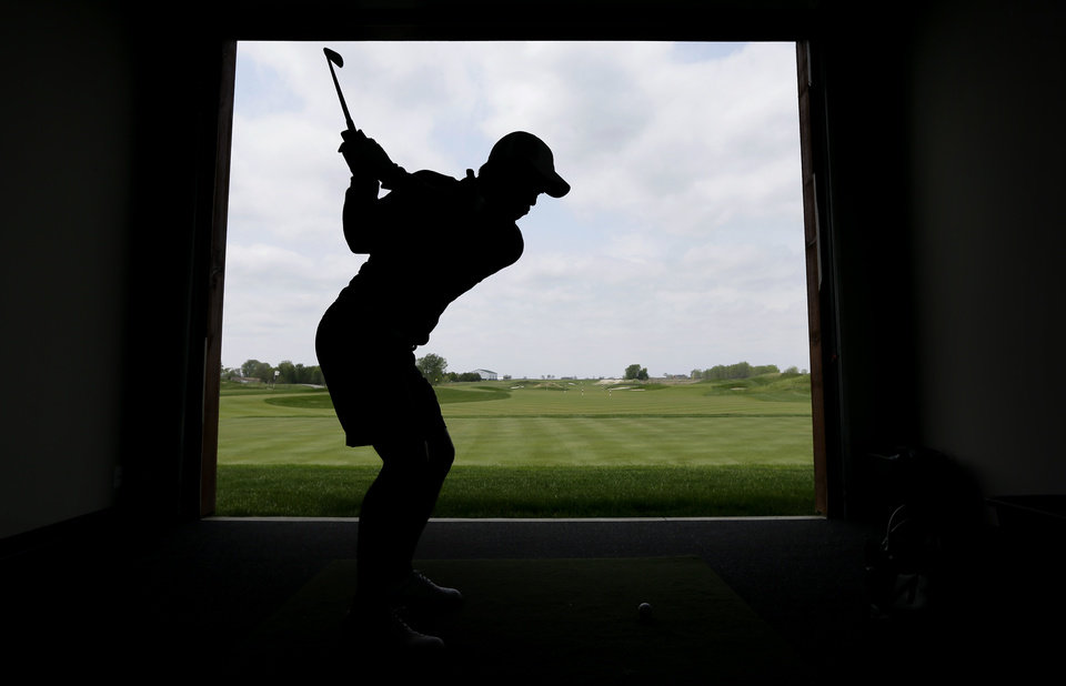Photo - Iowa State golfer Ruben Sondjaja hits a ball onto a practice range at the school's Golf Performance Center, Monday, May 19, 2014, in Ames, Iowa. Iowa State is headed to the NCAA tournament for the first time in 61 years, snapping one of the longest droughts. (AP Photo/Charlie Neibergall)