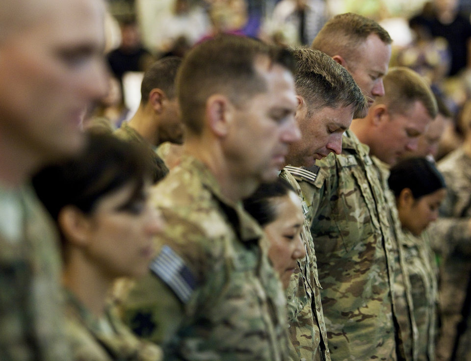 Returning soldiers pray during a homecoming ceremony for members of the Oklahoma National Guard\'s 45th Infantry Brigade Combat Team returning from Afghanistan at the Will Rogers Air National Guard Base in Oklahoma City, Friday, March 30, 2012. Photo by Nate Billings, The Oklahoman