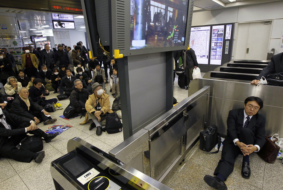 Photo - Stranded commuters watch a TV news on a powerful earthquake at Tokyo railway station as train services are suspended in Tokyo Friday, March 11, 2011. The largest earthquake in Japan's recorded history slammed the eastern coasts Friday. (AP Photo/Hiro Komae) ORG XMIT: TTX101