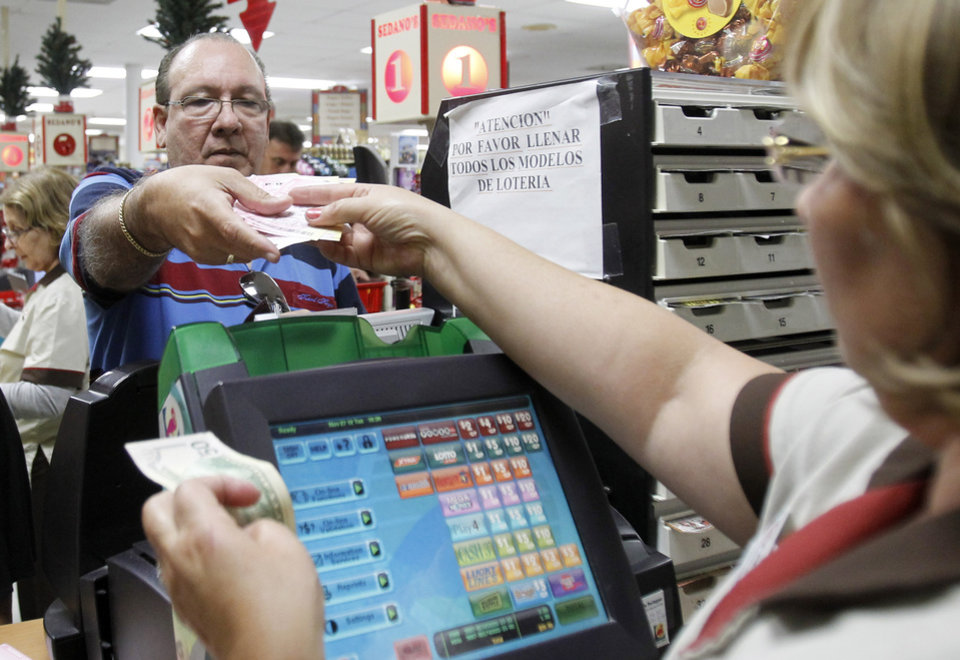 Photo -   Maria Diaz, right, sells a customer Powerball tickets at a local supermarket in Hialeah, Fla.,Tuesday, Nov. 27, 2012. There has been no Powerball winner since Oct. 6, and the jackpot already has reached a record level for the game. Already over $500 million, it is the second-highest jackpot in lottery history, behind only the $656 million Mega Millions prize in March. (AP Photo/Alan Diaz)