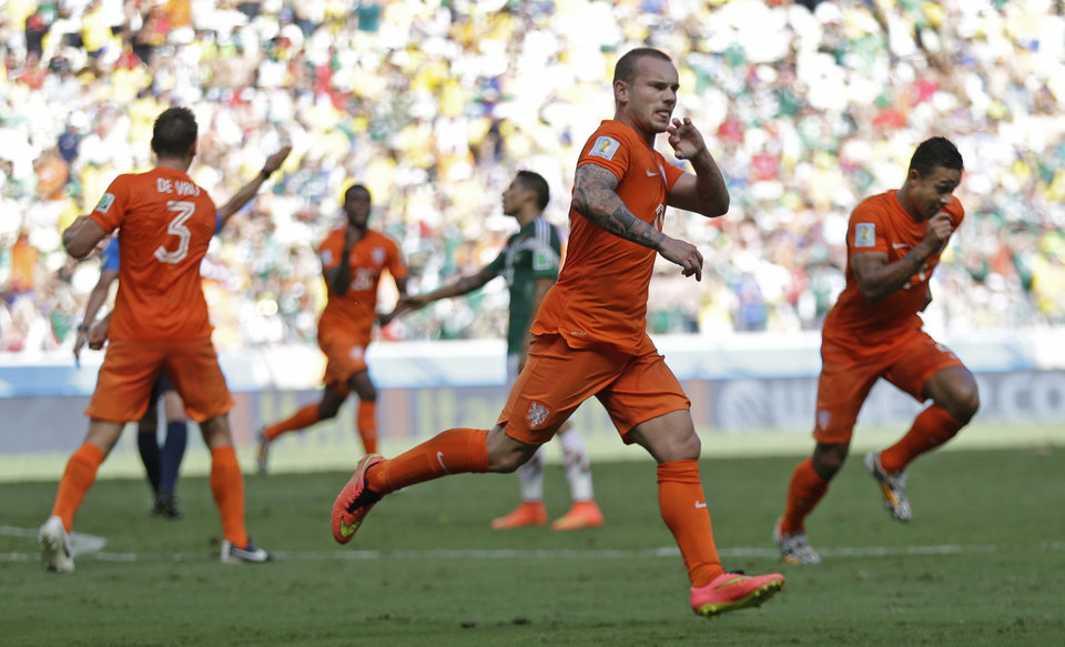 Photo - Netherlands' Wesley Sneijder, center, celebrates after scoring his side's first goal during the World Cup round of 16 soccer match between the Netherlands and Mexico at the Arena Castelao in Fortaleza, Brazil, Sunday, June 29, 2014. (AP Photo/Natacha Pisarenko)