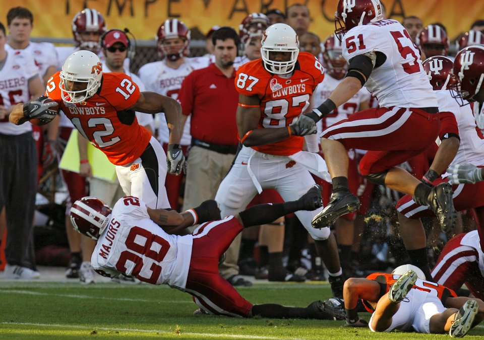 Photo - Oklahoma State's Adarius Bowman (12) is brought down by Indiana's Leslie Majors (28) in the first half during the Insight Bowl college football game between Oklahoma State University (OSU) and the Indiana University Hoosiers (IU) at Sun Devil Stadium on Monday, Dec. 31, 2007, in Tempe, Ariz. 