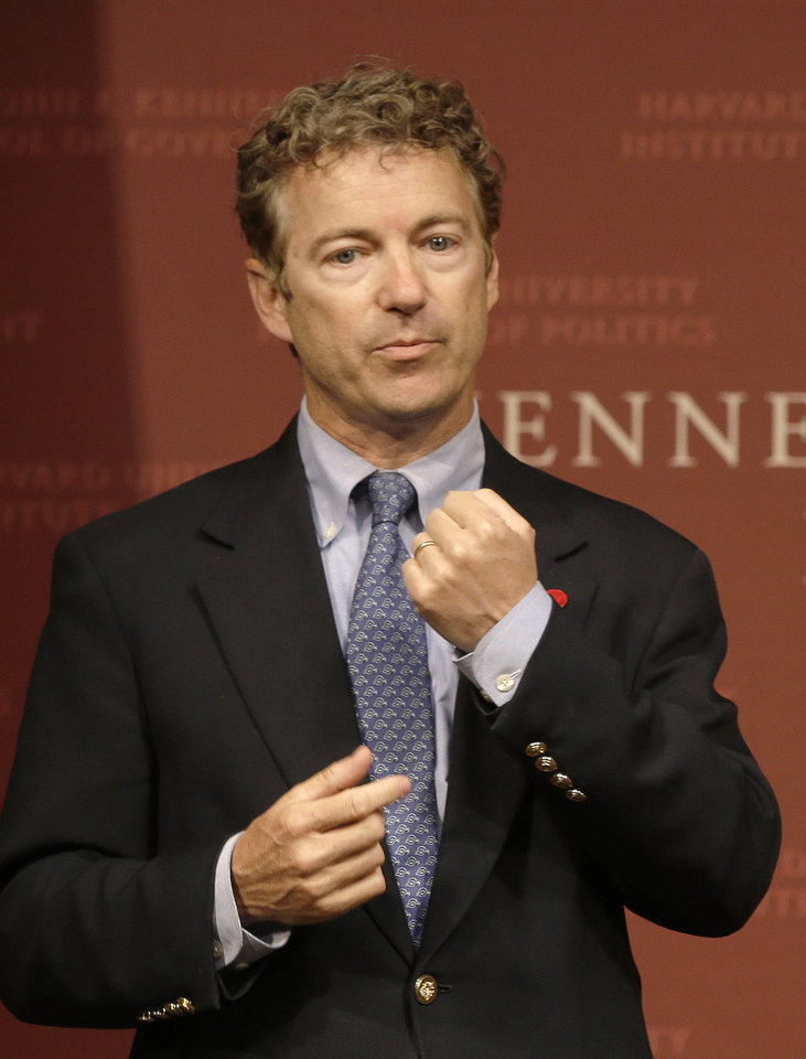 Photo - Sen. Rand Paul, R-Ky. gestures as he emphasizes a point during his public address at the John F. Kennedy Jr. Forum Institute of Politics at the Harvard Kennedy School, Friday April 25, 2014, in Cambridge, Mass. Fighting to move beyond his father's shadow, Paul is crafting new alliances with the Republican Party establishment during a Northeast tour that began Friday in Boston.  The 51-year-old Kentucky Republican, son of libertarian hero and former Texas Rep. Ron Paul, headlined an afternoon luncheon hosted by top lieutenants of former presidential nominee Mitt Romney _ a private meeting that comes as Paul weighs a 2016 presidential bid of his own.  (AP Photo/Stephan Savoia)