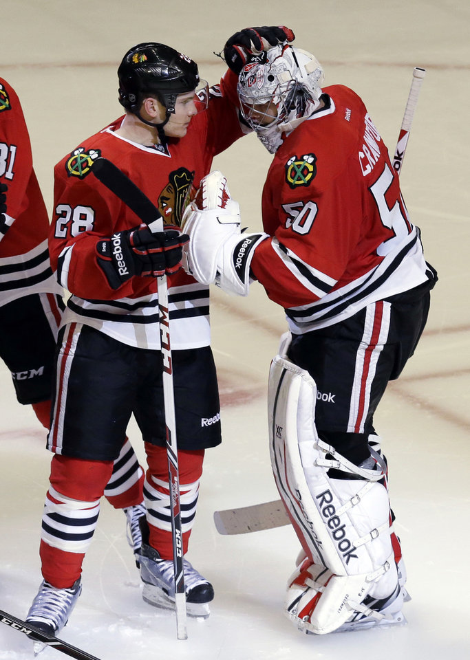Photo - Chicago Blackhawks goalie Corey Crawford, right, celebrates with Ben Smith after the Blackhawks defeated the Phoenix Coyotes 5-4 in a shootout during an NHL hockey game in Chicago, Thursday, Nov. 14, 2013. (AP Photo/Nam Y. Huh)