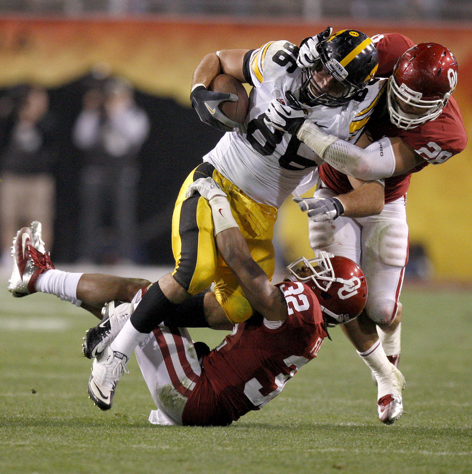 Oklahoma's Jamell Fleming (32) and Travis Lewis (28) bring down Iowa's C.J. Fiedorowicz (86) during the Insight Bowl college football game between the University of Oklahoma (OU) Sooners and the Iowa Hawkeyes at Sun Devil Stadium in Tempe, Ariz., Friday, Dec. 30, 2011. Photo by Bryan Terry, The Oklahoman