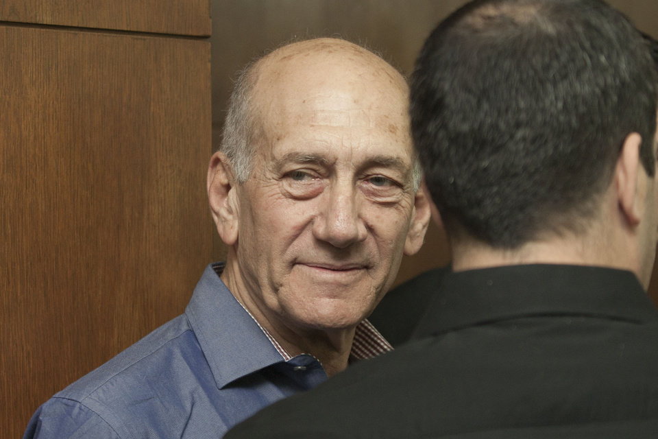 Photo - Former Israeli Prime Minister Ehud Olmert attends a hearing at Tel Aviv's District Court, Monday, March 31, 2014. The court handed down the verdict in the wide-ranging Jerusalem real estate scandal case related to Olmert's activities before becoming prime minister in 2006. A total of 13 government officials, developers and other businesspeople were charged in three separate schemes. (AP Photo/Dan Balilty, Pool)