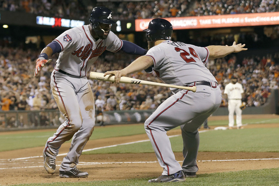 Photo - Atlanta Braves' Jason Heyward, left, is congratulated by Evan Gattis after scoring during the sixth inning of a baseball game against the San Francisco Giants in San Francisco, Tuesday, May 13, 2014. (AP Photo)