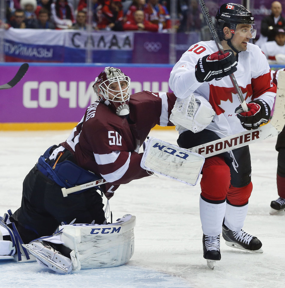 Photo - Latvia goaltender Kristers Gudlevskis, left, clears out  Canada forward Patrick Sharp from the crease during the second period of a men's quarterfinal ice hockey game at the 2014 Winter Olympics, Wednesday, Feb. 19, 2014, in Sochi, Russia. (AP Photo/Julio Cortez)