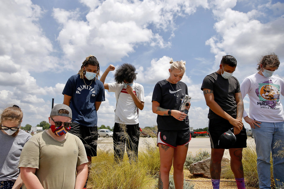 Photo - Protesters bow their heads during a moment of silence while protesting on the Main Street bridge over I-35 in Norman, Okla., Tuesday, June 2, 2020, in response to the death of George Floyd. [Sarah Phipps/The Oklahoman]