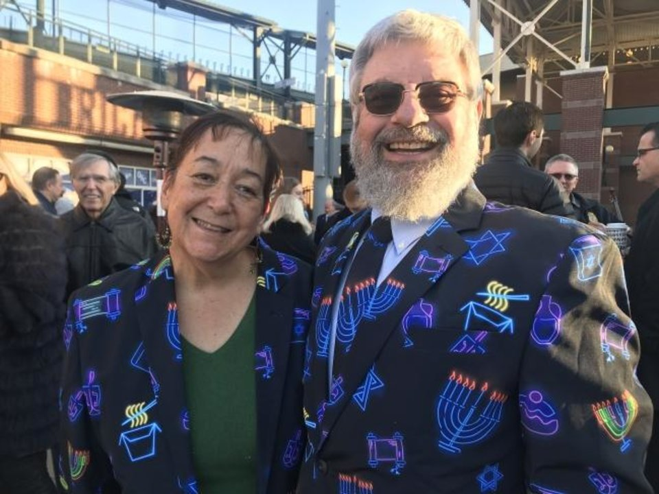 Photo -  Ronna and Larry Davis wore matching jackets featuring colorful menorahs and other symbols of the Jewish faith at the