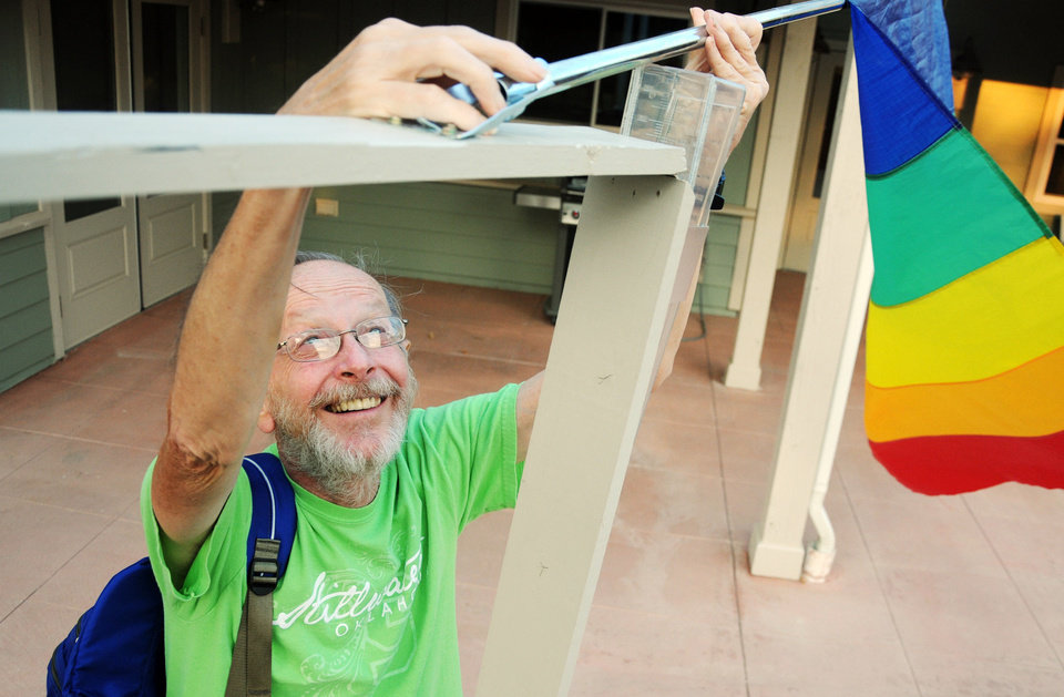 "John Wolfe, an Oakcreek Cohousing Community resident, hangs a flag on Sept. 12, 2013 to alert other community members that an event is about to happen. Wolfe says that when others see the flag, ""it lets them know an event is just about to start."" Photo by KT King/For the Oklahoman"