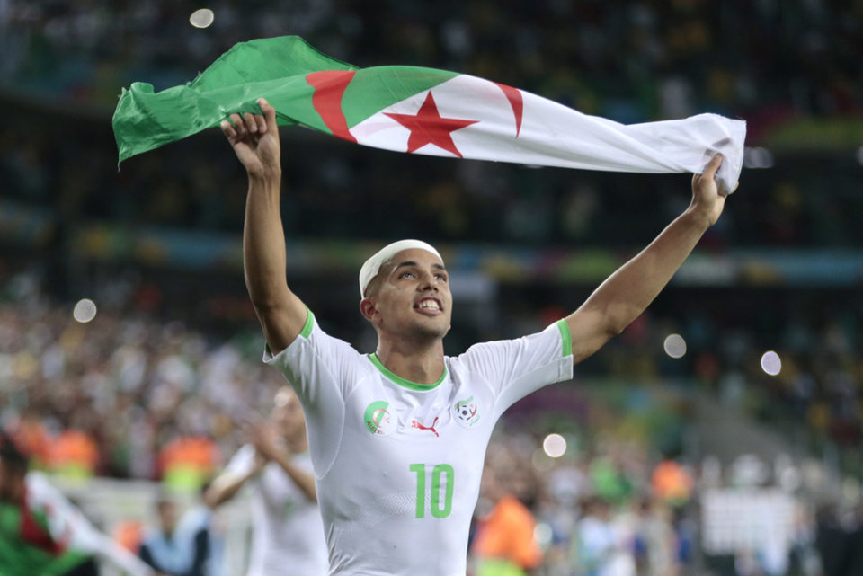 Photo - Algeria's Sofiane Feghouli celebrates after the group H World Cup soccer match between Algeria and Russia at the Arena da Baixada in Curitiba, Brazil, Thursday, June 26, 2014. The match ended in a 1-1 draw, but Algeria qualified for the round of 16. (AP Photo/Ivan Sekretarev)