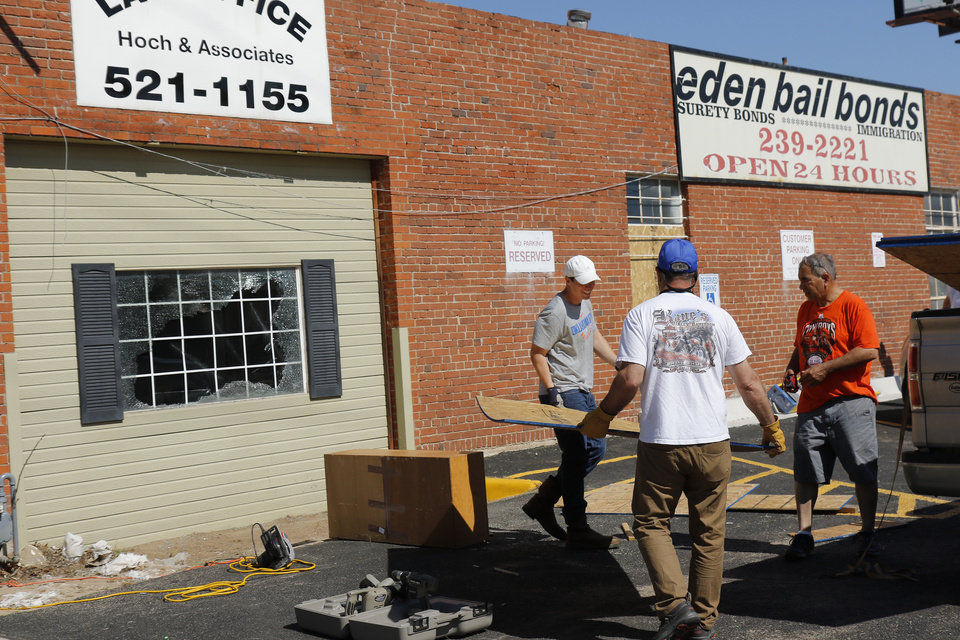 Photo - Crews measure a board to fit a broken window at Eden Bail Bonds and Hoch & Associates Lw Office on Shartel across from the Oklahoma County Jail Damage from Saturday night protest in downtown Oklahoma City, Sunday, May 31, 2020. [Doug Hoke/The Oklahoman]