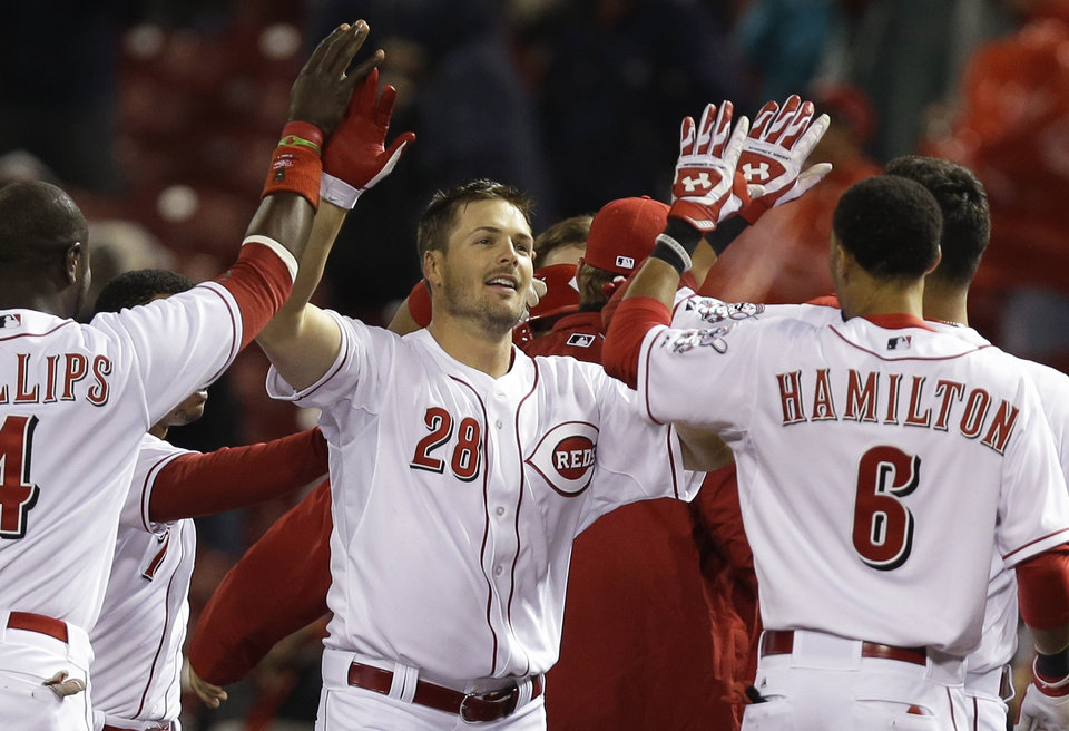 Photo - Cincinnati Reds' Chris Heisey (28) is congratulated by Brandon Phillips (4) and Billy Hamilton (6) after Heisey hit a bases-loaded single off St. Louis Cardinals relief pitcher Carlos Martinez to drive in the winning run in the bottom of the ninth inning of a baseball game, early Thursday, April 3, 2014, in Cincinnati. Cincinnati won 1-0. (AP Photo/Al Behrman)