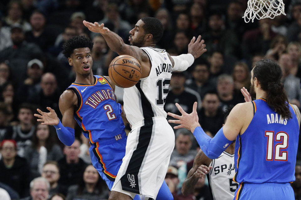 Photo - Oklahoma City Thunder guard Shai Gilgeous-Alexander (2) passes the ball past San Antonio Spurs center LaMarcus Aldridge, center, to teammate Steven Adams, right, during the second half of an NBA basketball game, in San Antonio, Thursday, Jan. 2, 2020. Oklahoma City won 109-103. (AP Photo/Eric Gay)
