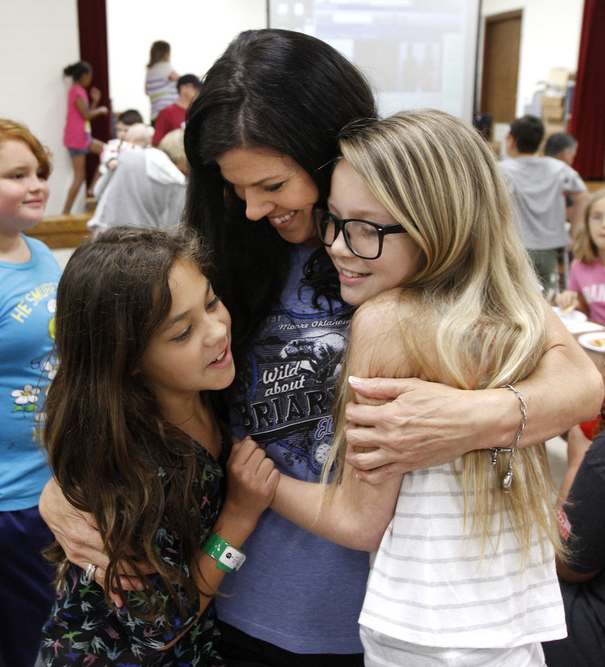 Photo - Briarwood Elementary School fifth graders Gabby Lara, left, and Ashley McClintick hug teacher Robin Dziedzic before receiving gifts from Martin Luther King Elementary School in Edison, New Jersey during a get-together at Red Oak Elementary School in Oklahoma City, OK, Saturday, June 15, 2013. Children from the two schools were trading letters before the May 20th tornado destroyed the school. Photo by Paul Hellstern, The Oklahoman