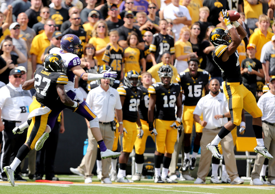 Photo - Iowa defensive back Greg Mabin, right, intercepts a pass intended for Northern Iowa wide receiver Brett LeMaster late in the fourth quarter of an NCAA college football game Saturday, Aug. 30, 2014, in Iowa City, Iowa. Iowa won the game 31-23. (AP Photo/Justin Hayworth)