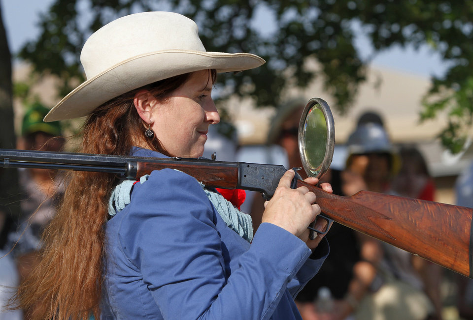 Marna Davis portrays  Old West sharpshooter and trick shot expert Annie Oakley. She and her husband, Doug,  who,plays the role of Oakley's husband and partner, Frank Butler, are from Hitchcock, Oklahoma.  Here, Davis is demonstrating a  trick shot by shooting a rifle balanced on her shoulder and looking into a mirror to see the target.  The Davis'  are part of free entertainment for visitors to the Pawnee Bill Ranch and Museum during the afternoon on performance dates.  Historically accurate accurate entertainment is free and takes place on grounds of the museum and mansion before the  Pawnee Bill Wild West Show starts.  Photo taken  Saturday,  June 23, 2012.  Photo by Jim Beckel, The Oklahoman