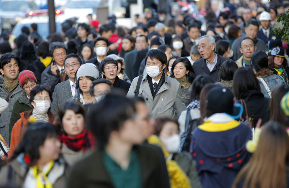 Photo - A crowd of people walk in a Tokyo street as no public transport became available after a strong earthquake hit eastern Japan Friday, March 11, 2011. (AP Photo/Itsuo Inouye) ORG XMIT: XITS110