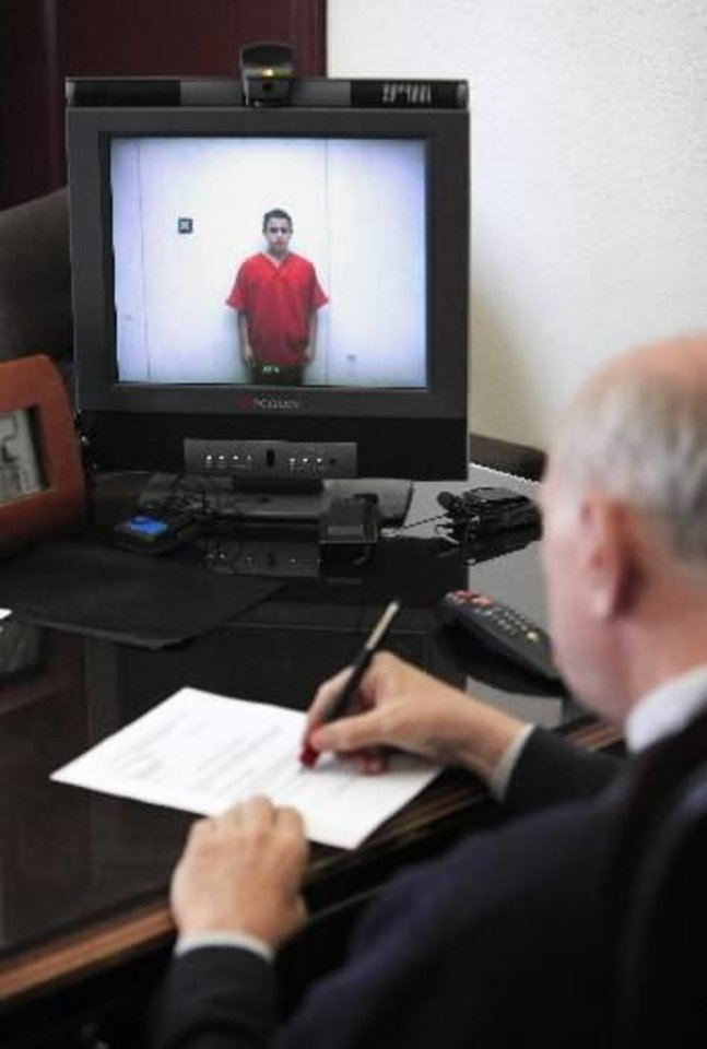 Tristan Owen, 15, appears from the Oklahoma County Jail in a monitor during his video arraignment in the chamber of Special Judge Russell Hall at the Oklahoma County Courthouse in Oklahoma City Friday, July 15, 2011. Photo by Paul B. Southerland, The Oklahoman