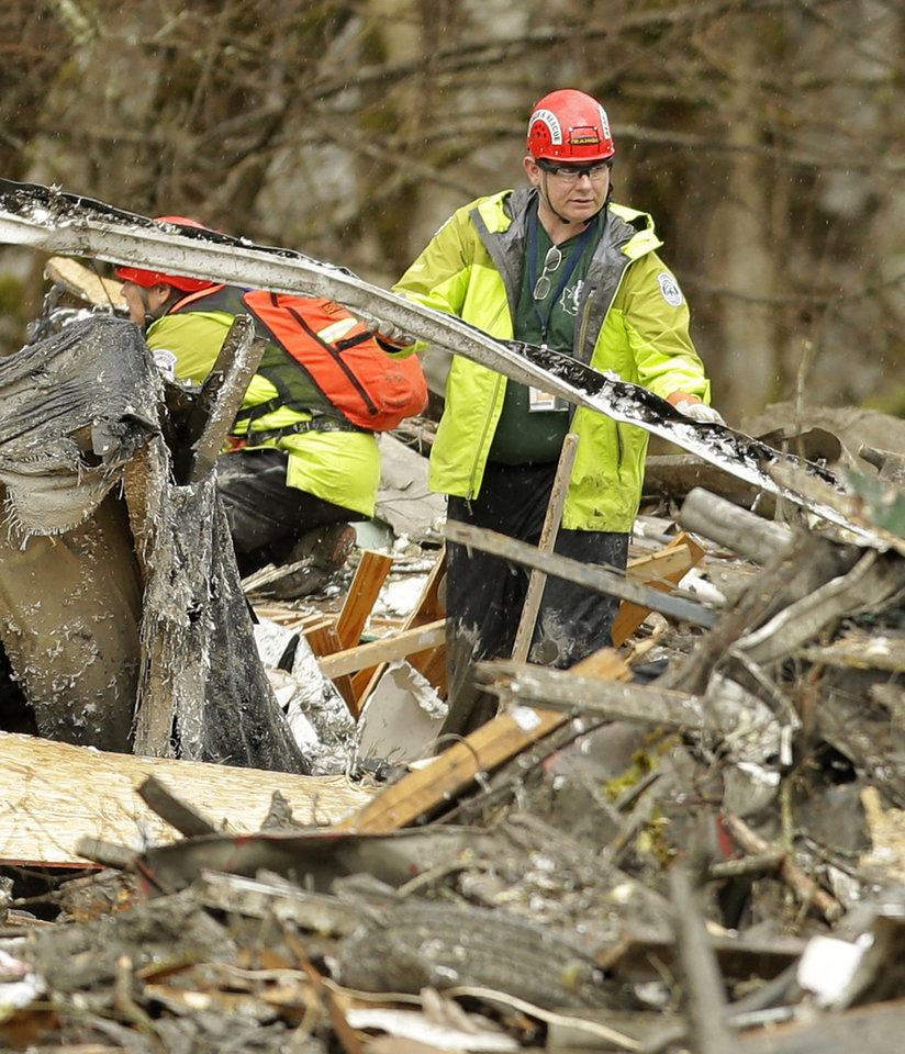 Photo - A search and rescue worker clears debris from a house Tuesday, March 25, 2014, on the western edge of the massive mudslide that struck near Arlington, Wash., on Saturday, killing at least 14 people and leaving dozens missing. (AP Photo/Ted S. Warren, Pool)