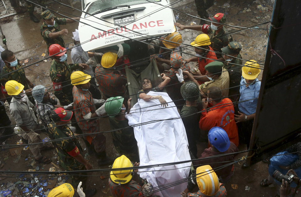 Photo - A survivor is carried on a stretcher into a waiting ambulance after being evacuated from a garment factory building that collapsed Wednesday in Savar, near Dhaka, Bangladesh, Saturday, April 27, 2013. Police in Bangladesh took five people into custody in connection with the collapse of a shoddily-constructed building this week, as rescue workers pulled 19 survivors out of the rubble on Saturday and vowed to continue as long as necessary to find others despite fading hopes.(AP Photo/Wong Maye-E)