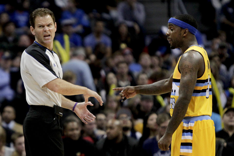 Photo - Referee Mark Ayotte, left, and Denver Nuggets' Ty Lawson, right, discuss a call during the first quarter of an NBA basketball game against the Oklahoma City Thunder, Thursday, Jan. 9, 2014, in Denver. (AP Photo/Barry Gutierrez)