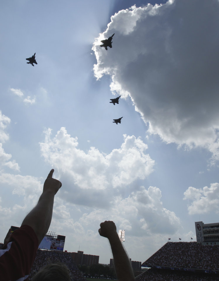 Fans cheer at a fly over by Air Force jets before the college football game between the University of Oklahoma Sooners (OU) and the Air Force Falcons at Gaylord Family-Oklahoma Memorial Stadium on Saturday, Sept. 18, 2010, in Norman, Okla.   Photo by Steve Sisney, The Oklahoman