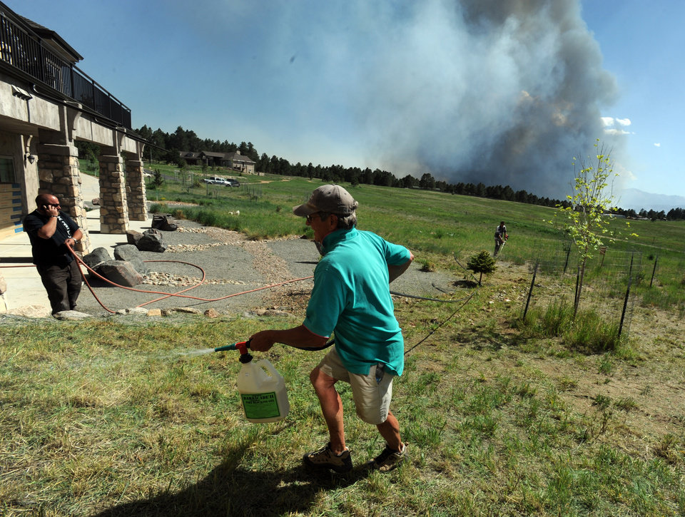Photo - Lynd Fitzgerald sprays fire retardant around a house while a fire burns out of control in the background north of Shoup Road and East of Highway 83 in Colorado Springs, Colo. on Tuesday afternoon, June 11, 2013.  The Black Forest Fire was one of at least three significant wildfires burning in Colorado amid gusty winds and record-breaking hot, dry weather. (AP Photo/The Colorado Springs Gazette, Christian Murdock) MAGS OUT